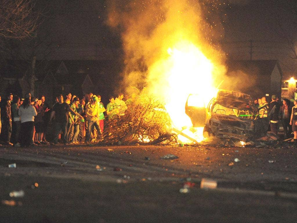 Young St Patrick's Day revellers gather round the street blaze in London, Ontario