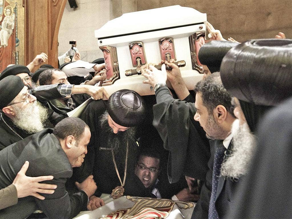 Pallbearers struggle to carry the coffin of Coptic Pope Shenuda III out of Saint Mark's cathedral during his funeral service yesterday