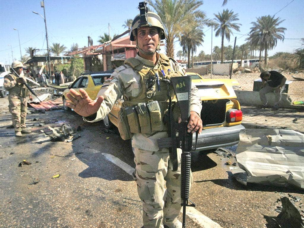 Security forces stand guard at the site of the bomb attack in Kerbala