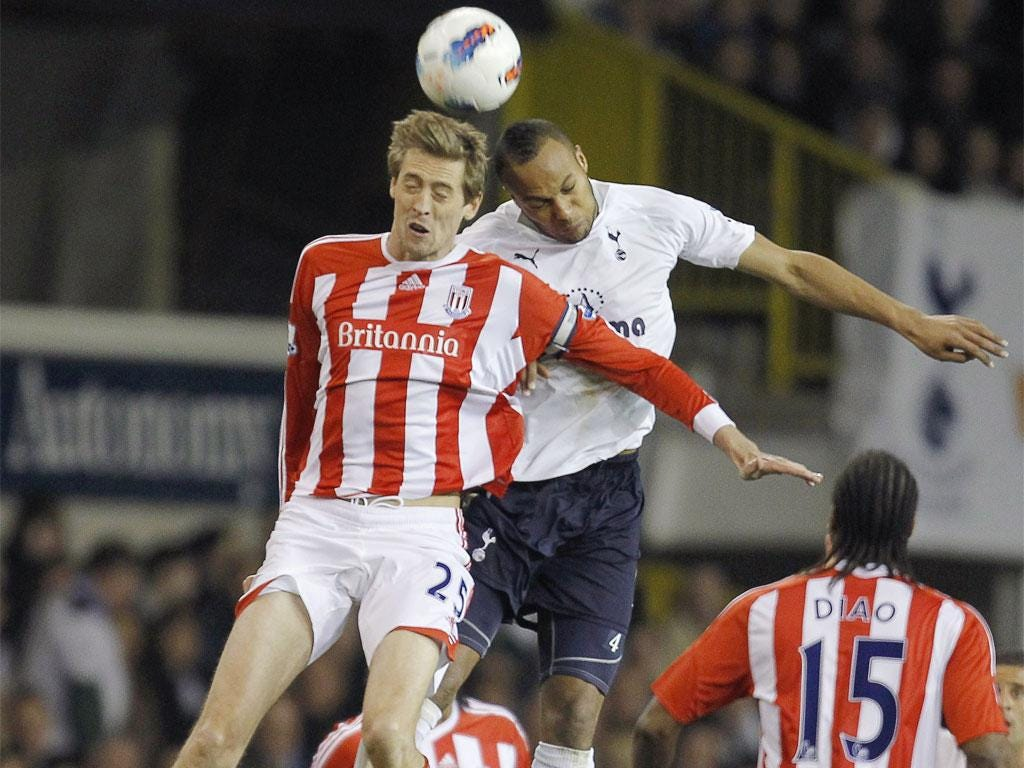 Spurs' Peter Crouch and Stoke's Younes Kaboul compete to win a header