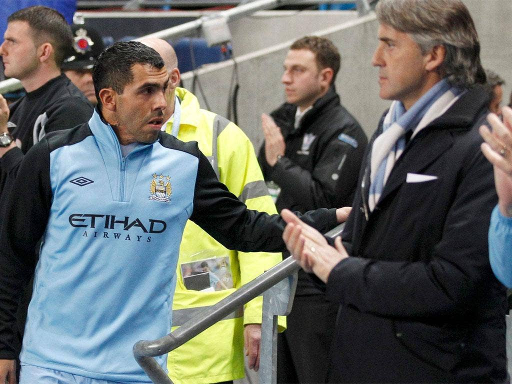 Carlos Tevez walks past his manager Roberto Mancini and on to the bench before last night's match with Chelsea at the Etihad