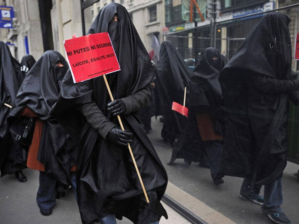 A Muslim woman protests in France with a sign that reads 'Neither sluts, nor submissives. Secularism, equality, diversity'
