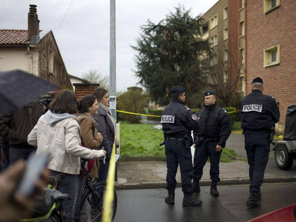 Passers by look on as French police officers block the street in front of Mohamed Merah's apartment building in Toulouse