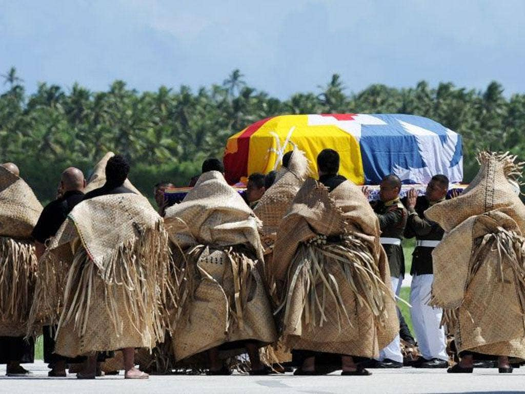 The casket carrying the body of King George Tupou V is draped in the Tongan royal standard upon its arrival at Fua'amotu International Airport