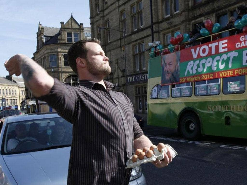 The protester throws eggs prior to George Galloway's victory parade in Bradford