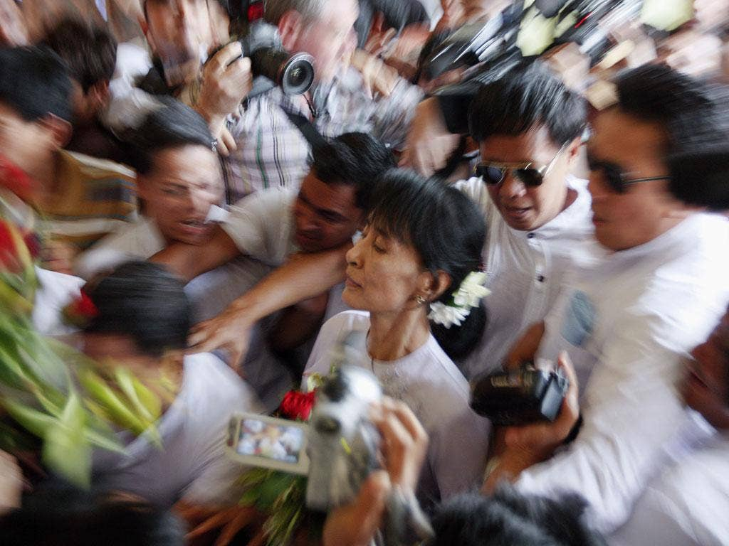 April 2, 2012: Myanmar's pro-democracy leader Aung San Suu Kyi makes her way through the crowd as she arrives to the office of her National League for Democracy (NLD) in Yangon. Aung San Suu Kyi won a seat in parliament on Sunday, her party said, after an