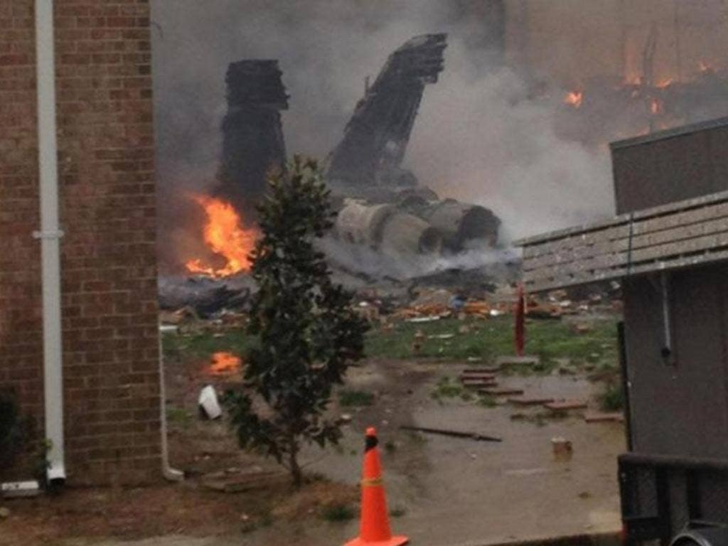 The burning fuselage of an F/A-18 Hornet lies smoldering after crashing into a residential building in Virginia Beach