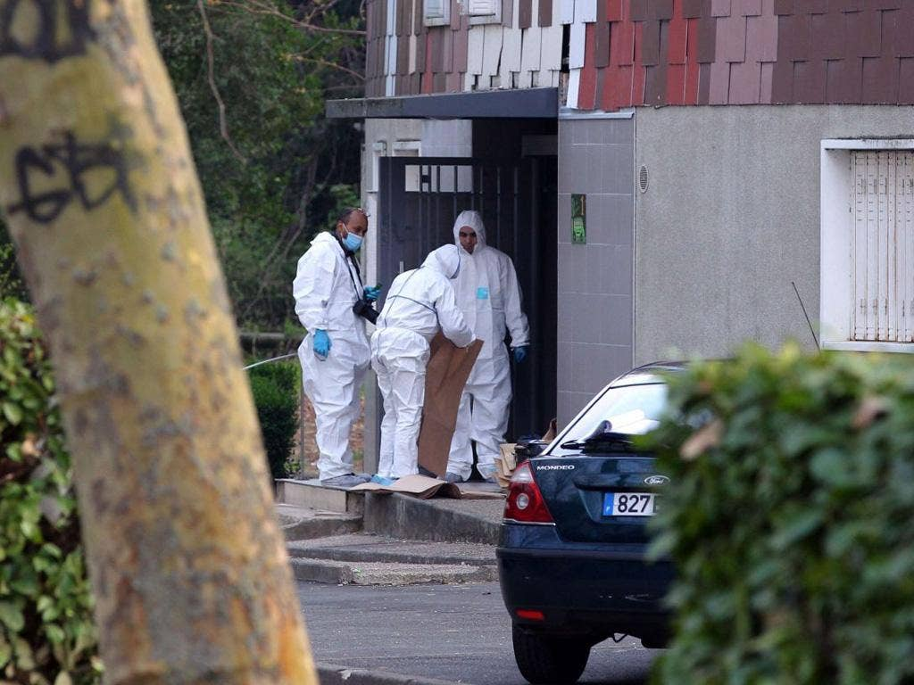 Forensic detectives look for clues at the flats in Grigny where a woman aged 47 was shot on Thursday