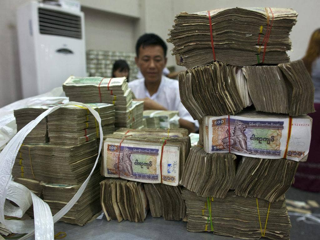 Workers count Burmese kyat currency at a bank in Rangoon. Washington said this week it would begin lifting some sanctions on what the IMF calls 'the next economic frontier in Asia'