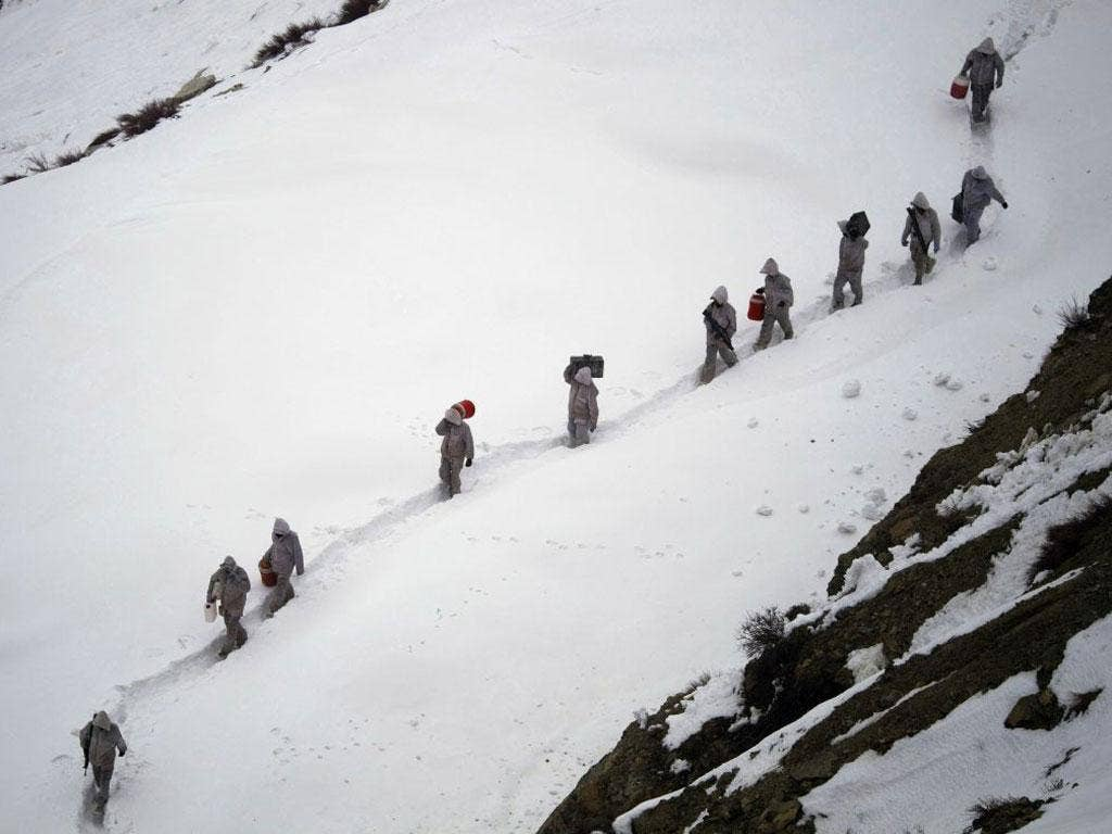 Pakistani soldiers carry supplies down the glacier, near the disaster site