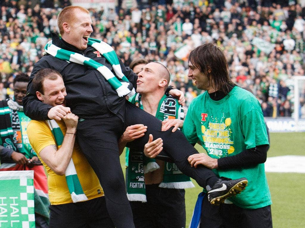 Happy Hoops: Celtic manager Neil Lennon gets a lift from Anthony Stokes, Scott Brown and Georgios Samaras after the club clinch the Scottish Premier title