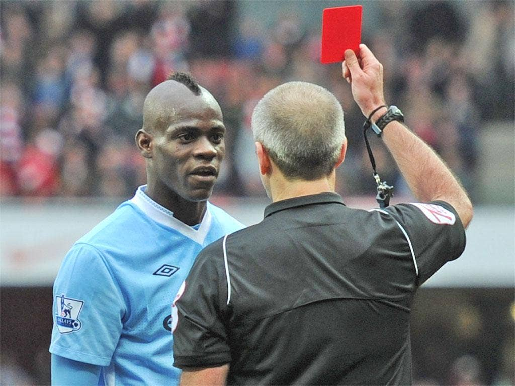 Mario Balotelli is shown red by Martin Atkinson after his stamp on Arsenal's Alex Song