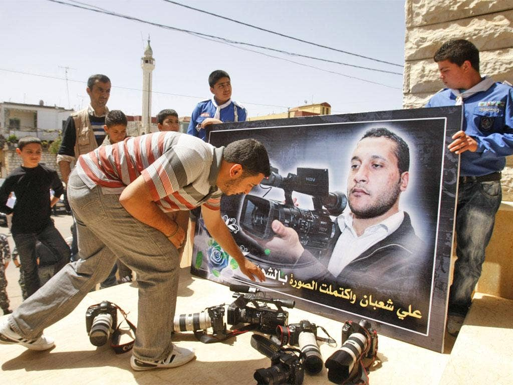 Colleagues laying down cameras in front of a portrait of the Lebanese cameraman Ali Shabaan at his funeral in the village of Maifadoun