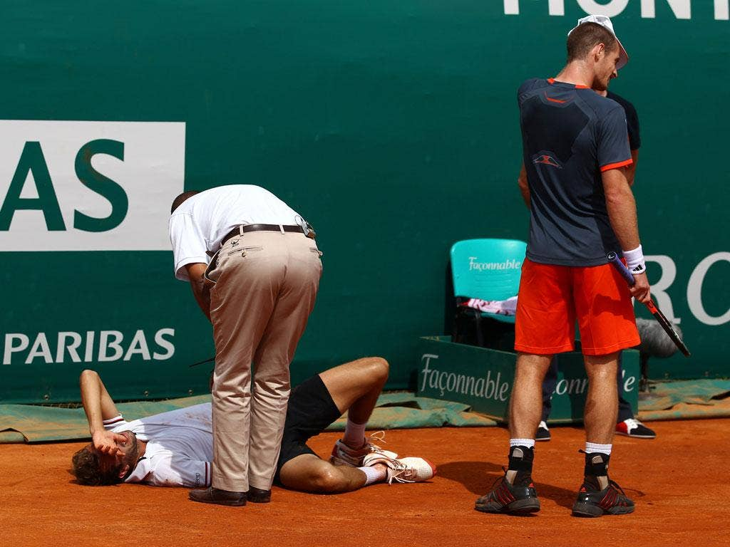 Andy Murray of Great Britain looks away as an injured Julien Benneteau of France receives help