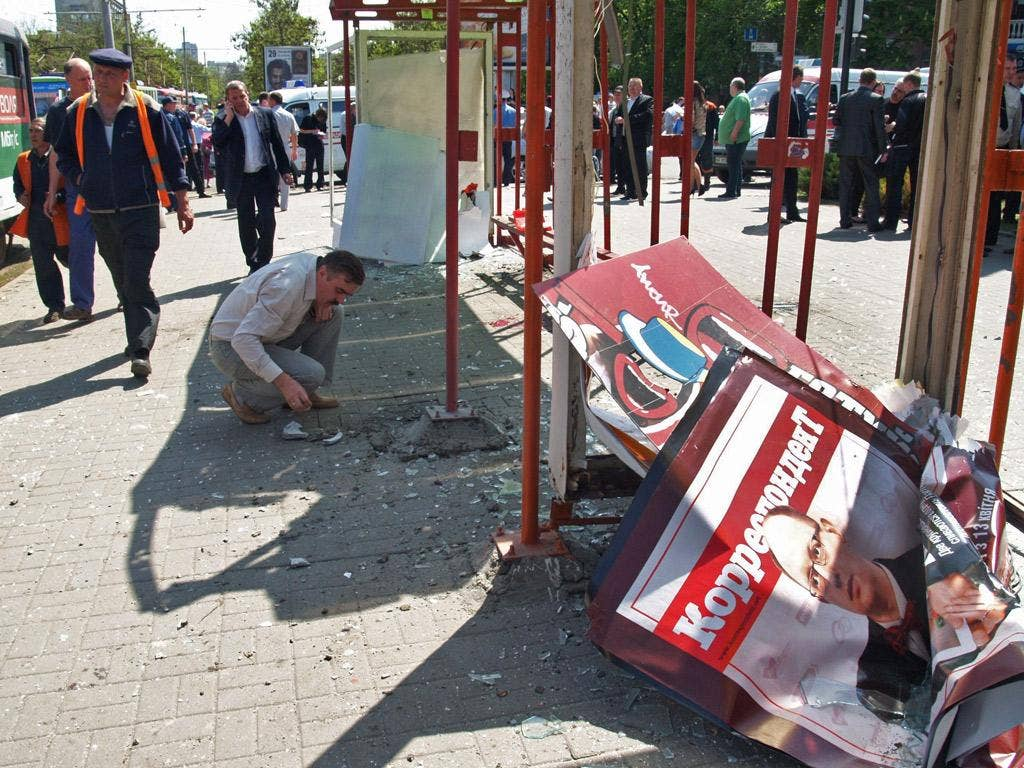Ukrainian authorities examine the scene of an explosion at a tram stop in Dnipropetrovsk