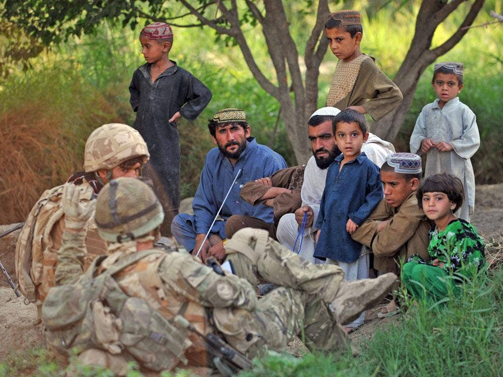 INVASION: British soldiers with Afghan locals during a patrol in 2010