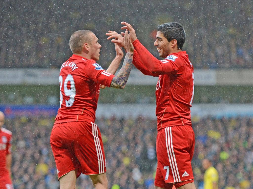 Red glow: Luis Suarez celebrates his Liverpool hat-trick at Carrow Road with fellow striker Craig Bellamy
