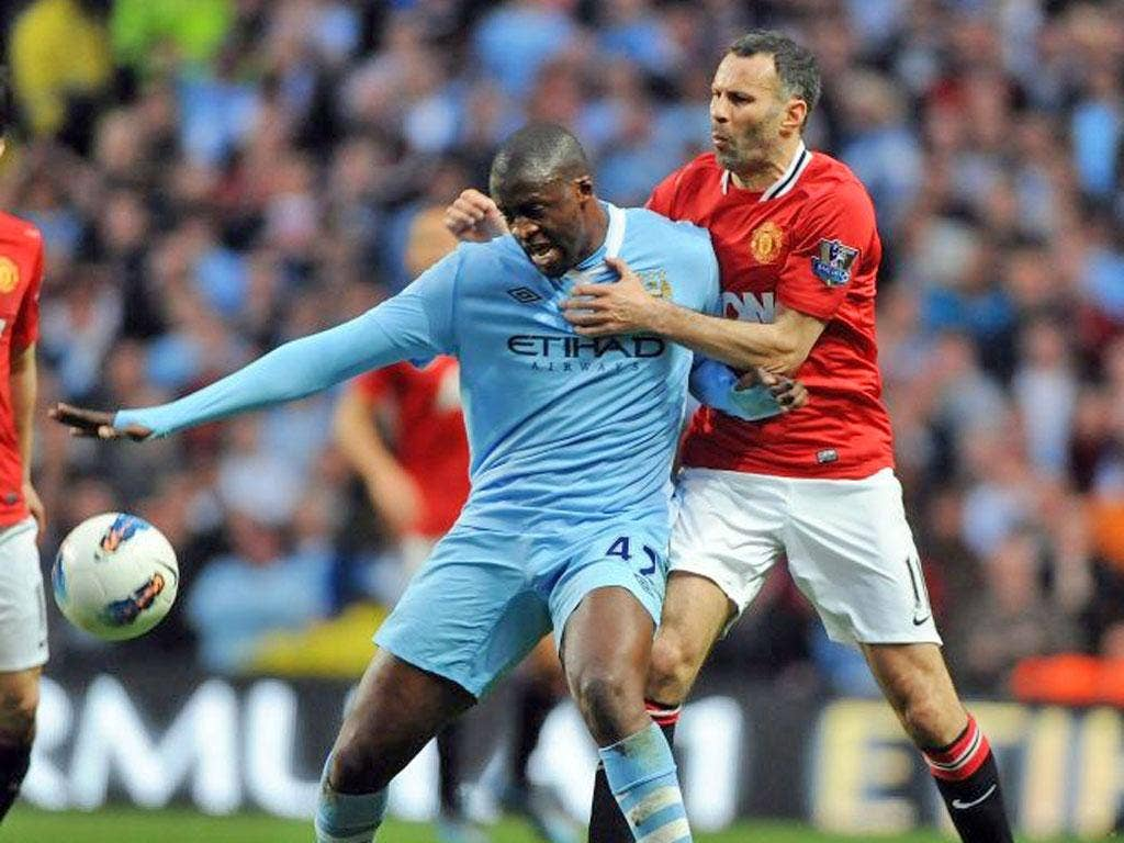 Ryan Giggs tries to get to grips with Yaya Touré