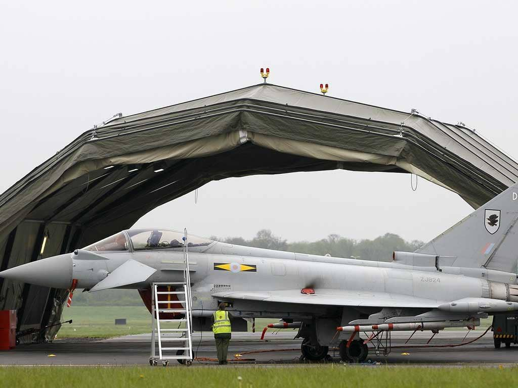 Ground technicians work on a Typhoon fighter aircraft at RAF base Northolt