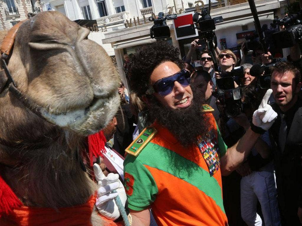 Sacha Baron Cohen dressed as Admiral General Aladeen poses with a camel in Cannes