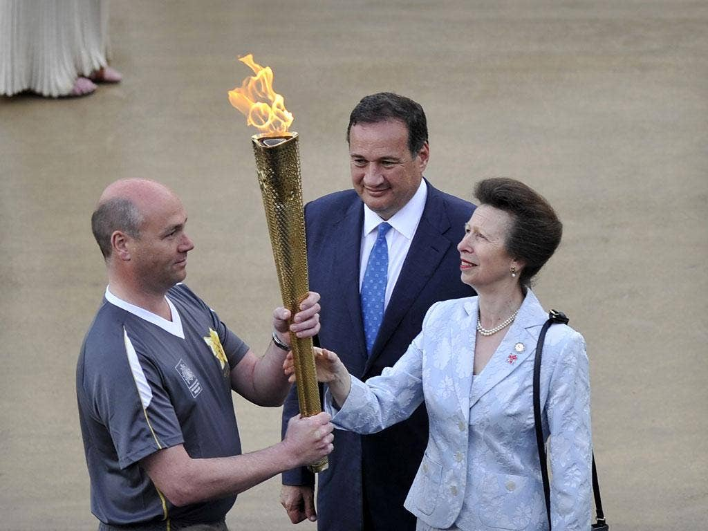 Princess Anne of Britain hands over the torch with the olympic flame to be prepared for the journey to London