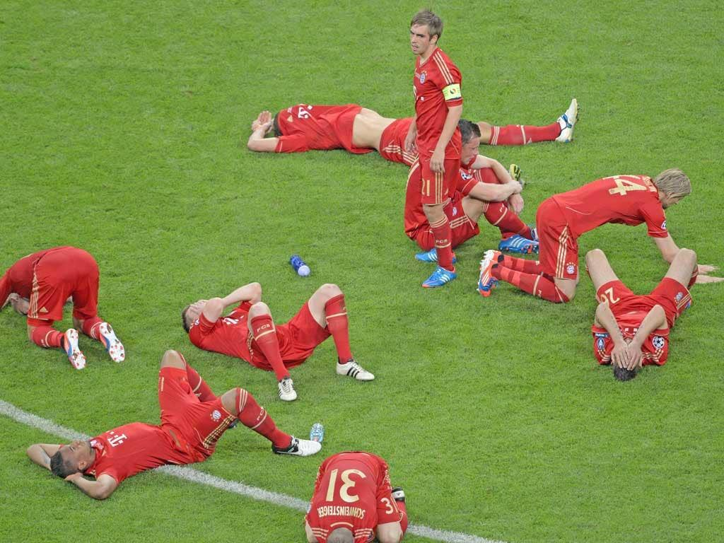 Distraught Bayern Munich players are slumped around captain Philipp Lahm after their defeat