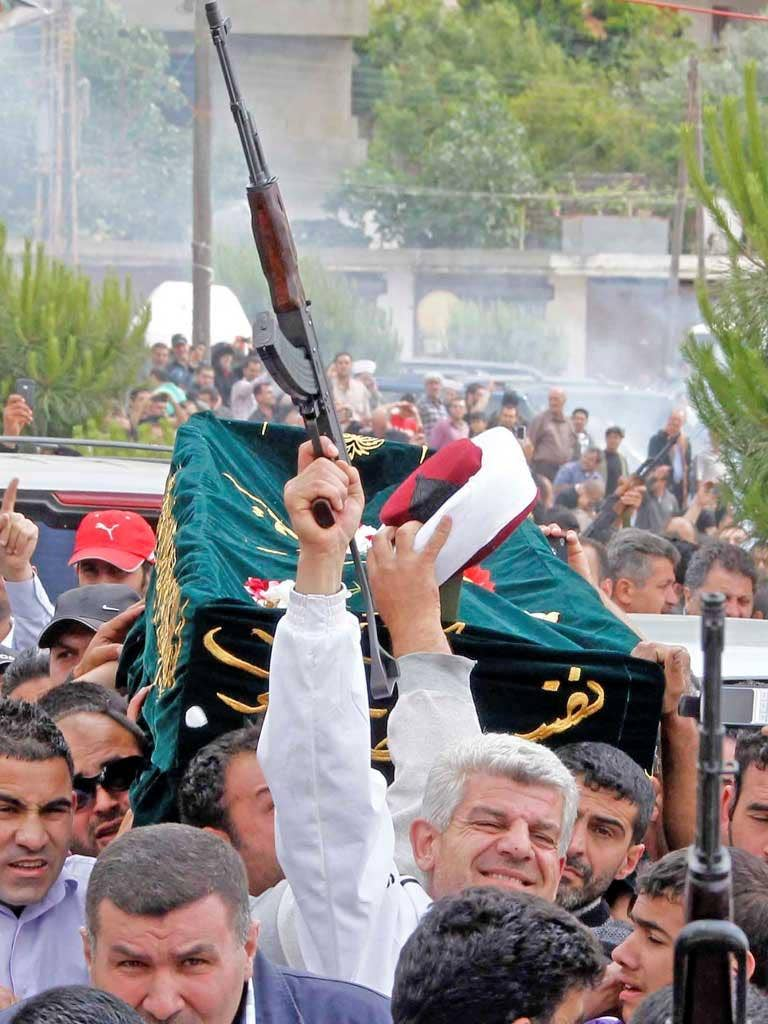 A mourner fires his rifle as the coffin and turban of Sunni cleric Sheikh Ahmed Abdul-Wahid is carried through his home town