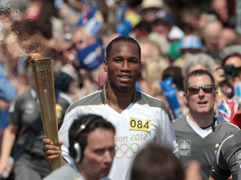Drogba, who announced yesterday he was quitting Chelsea, waved at supporters as he jogged through the town centre with his torch