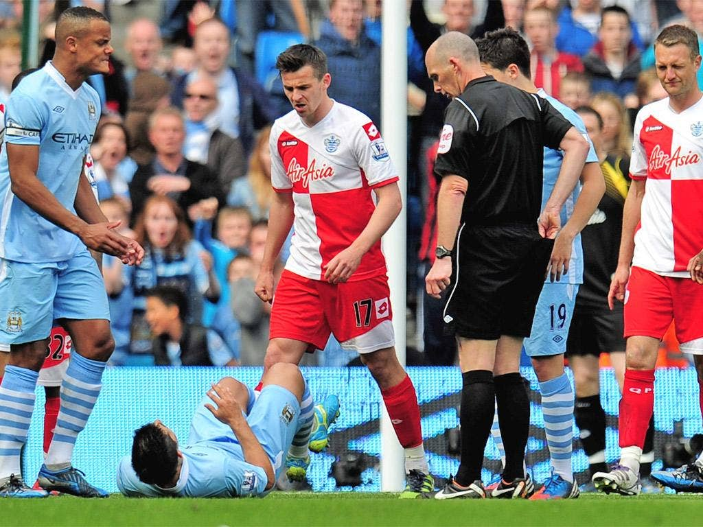 Joey Barton stands over Manchester City's Sergio Aguero, after being sent off by Mike Dean