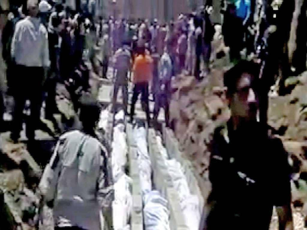 Video published on the internet shows bodies being prepared in Houla for a mass funeral