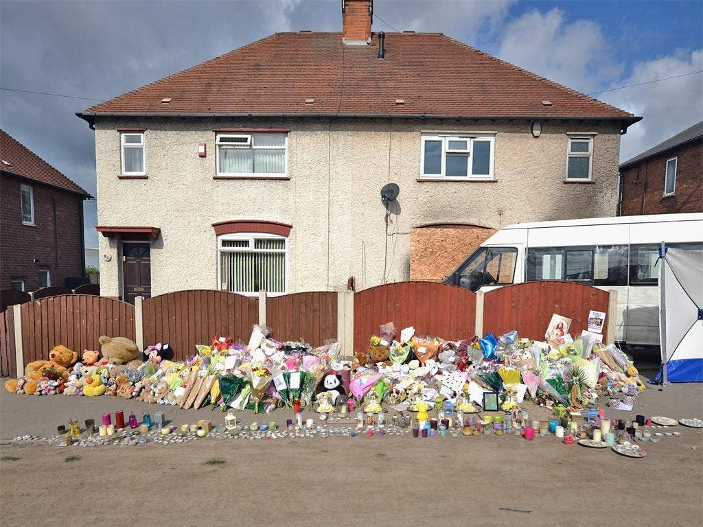 Floral tributes adorn the pavement outside the house in Allenton, Derby