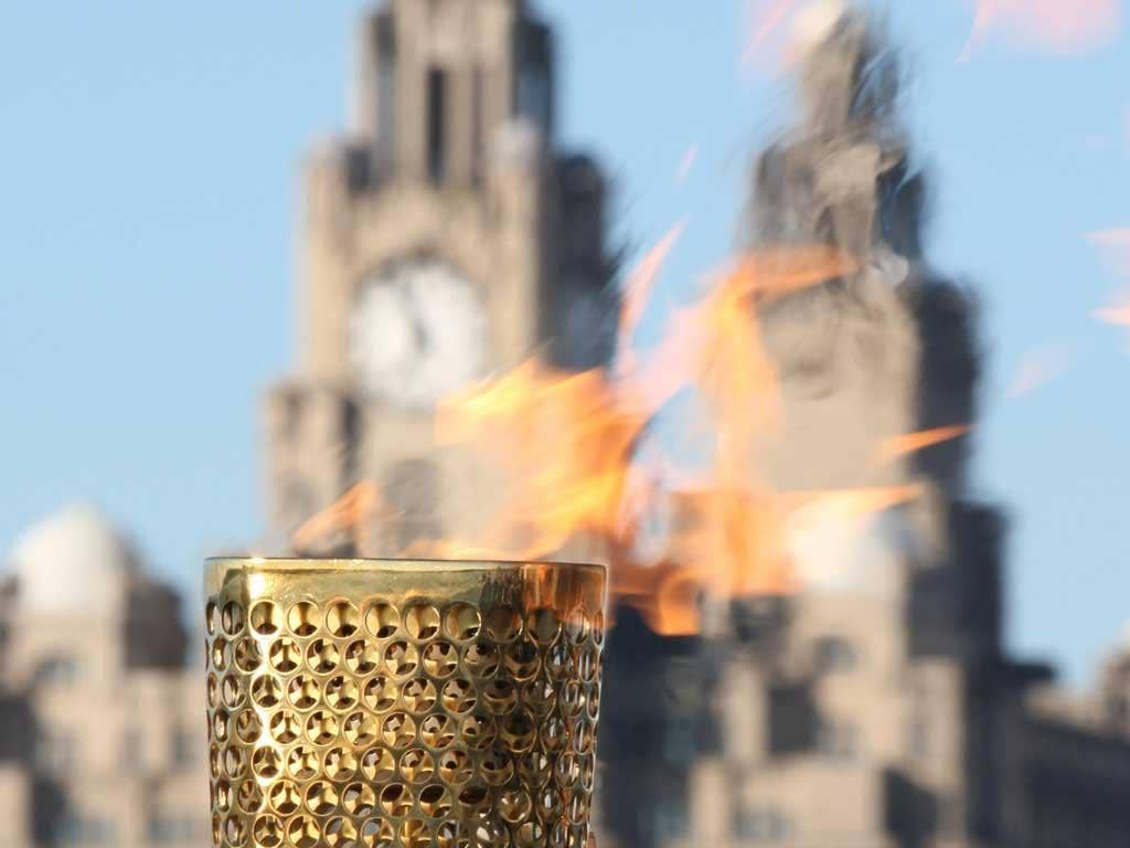 Flaming June: The Olympic torch pauses in Liverpool during its long journey around the United Kingdom before the Games begin in London next month