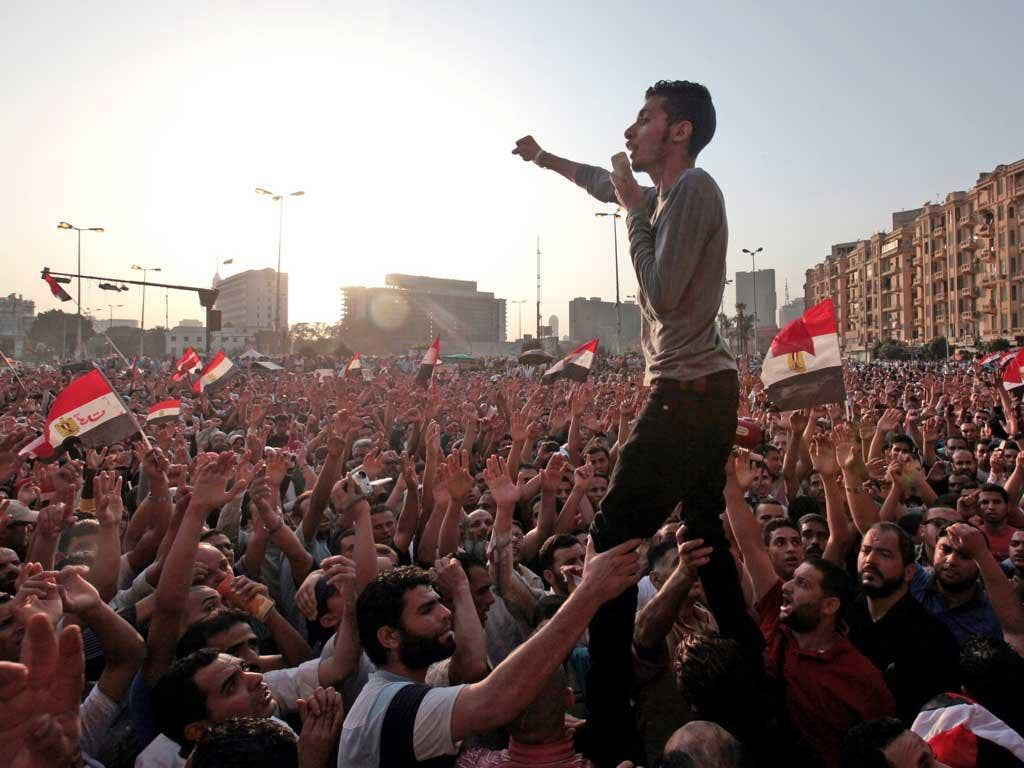 Thousands of protesters gather in Cairo yesterday to wave national flags and chant anti-military slogans