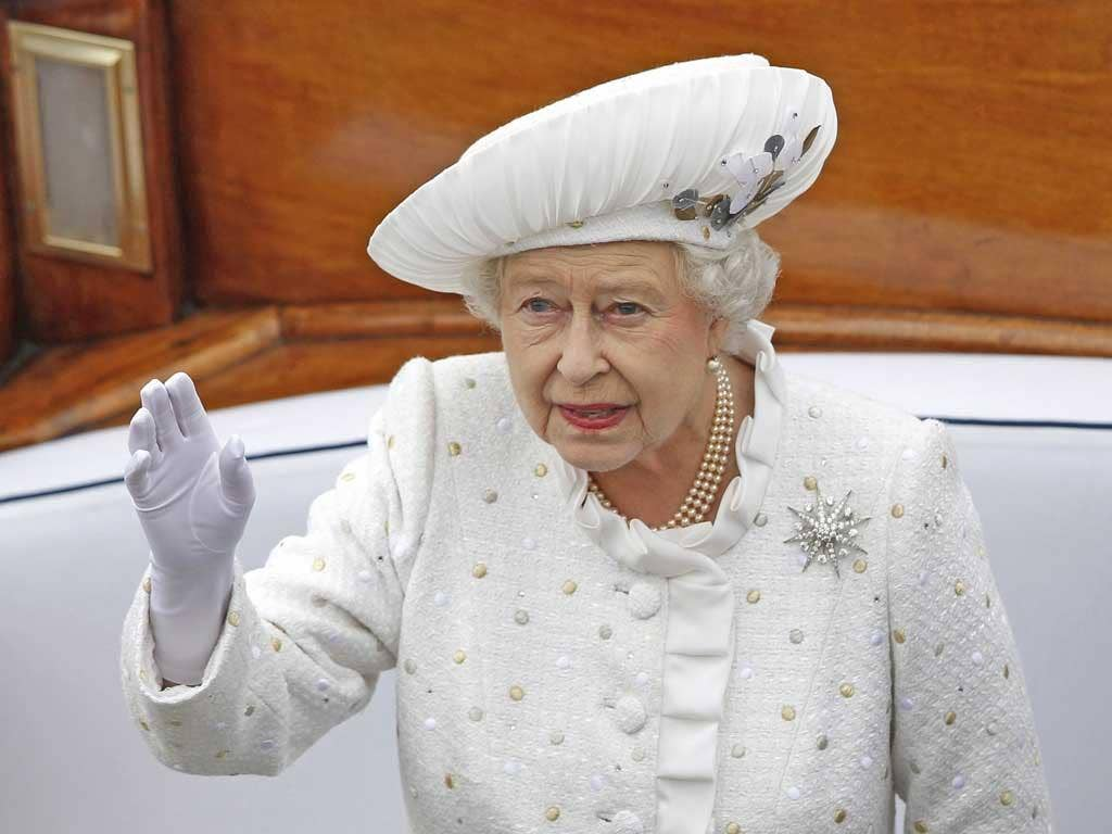 Queen Elizabeth waves from a boat during a pageant in celebration of her Diamond Jubilee along the River Thames