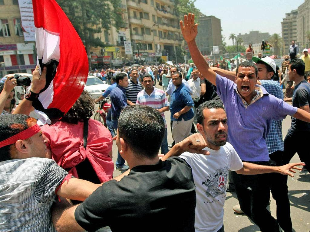 Protesters scuffle with supporters of Ahmed Shafiq on Tahrir Square yesterday