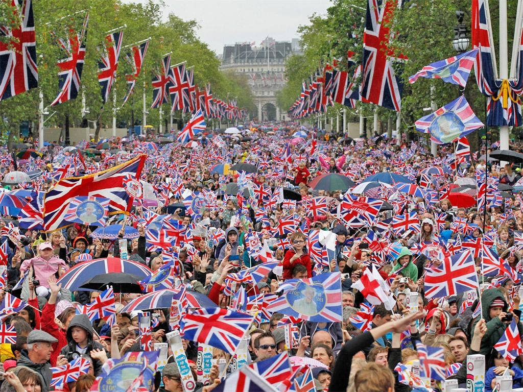 Revelers crowd the Mall to watch The Queen appear on the Buckingham Palace balcony