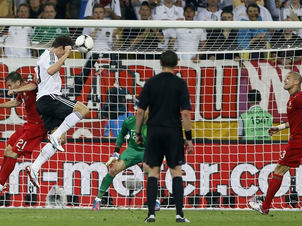 Germany's Mario Gomez, second left, heads the ball into the goal during the Euro 2012 game against Portugal