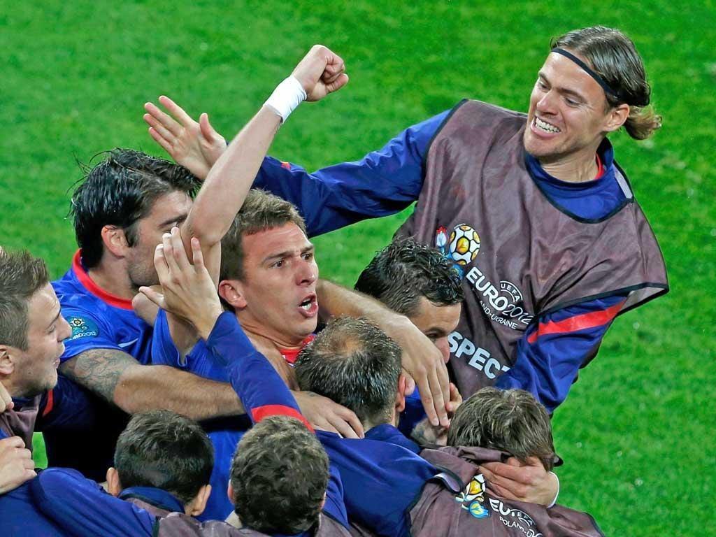 Mario Mandzukic celebrates with the Croatia team after his early goal