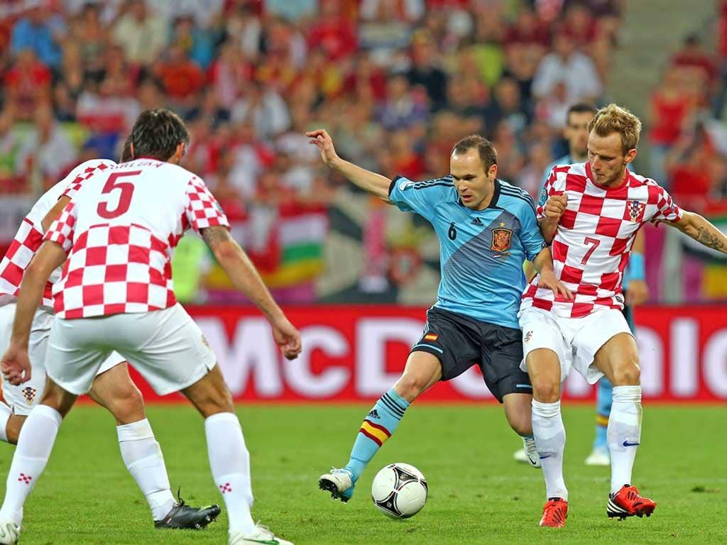 Andres Iniesta of Spain and Ivan Rakitic of Croatia compete for the ball during the UEFA EURO 2012 group C match