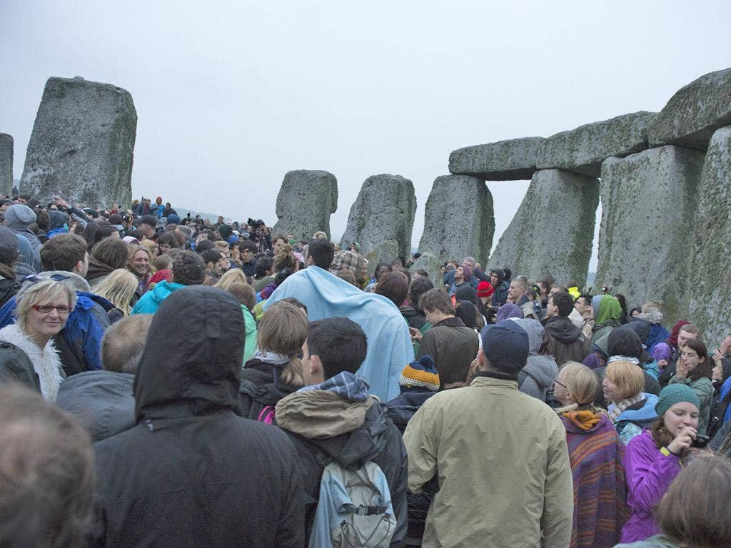 Poor weather could not dampen the spirits of 14,500 people who welcomed the sun at Stonehenge at dawn this morning.