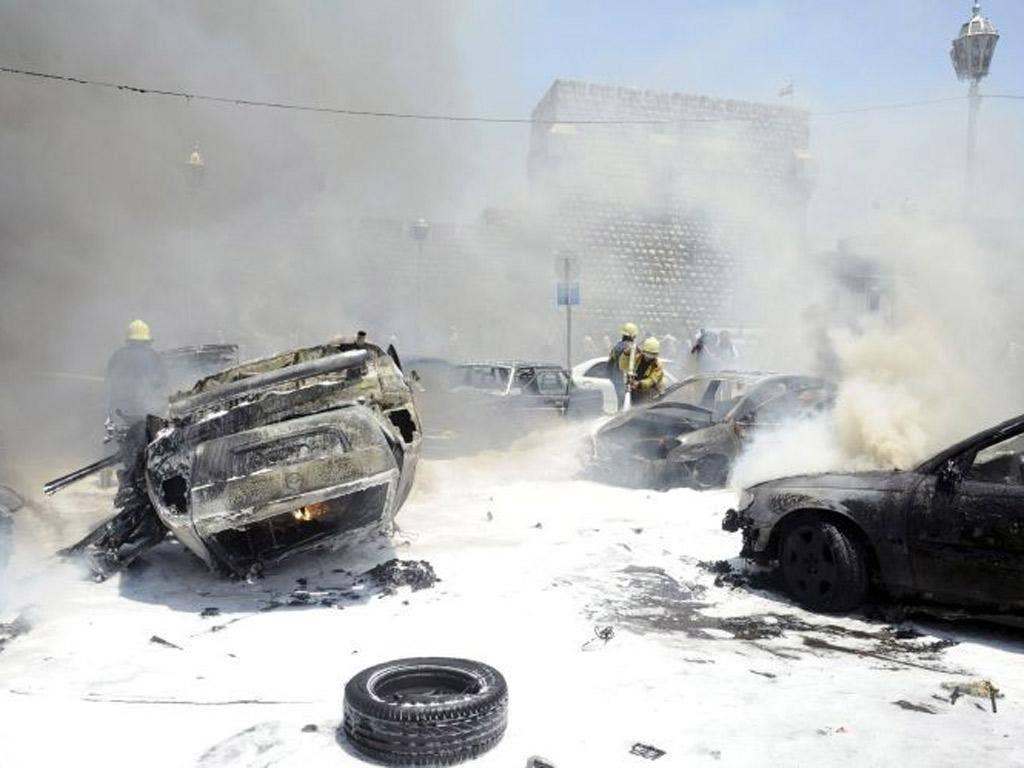 Civil Defence members extinguish fires on cars at the site of an explosion outside Syria's highest court in central Damascus