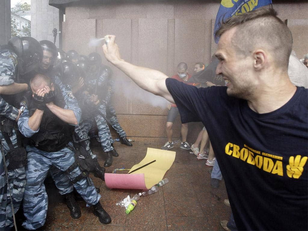 Pro-Ukrainian protesters spray tear gas at riot police near the parliament building in Kiev yesterday
