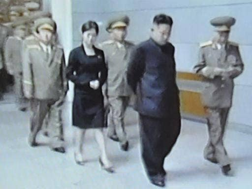 North Korean TV shows an unidentified woman close behind Kim Jong-un