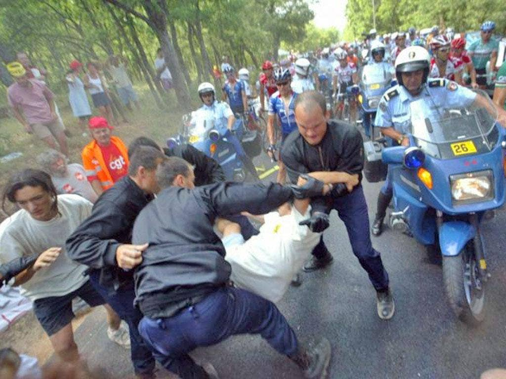 Police remove anti-globalisation demonstrators holding up the 10th stage of the 2003 Tour de France between Gap and Marseilles
