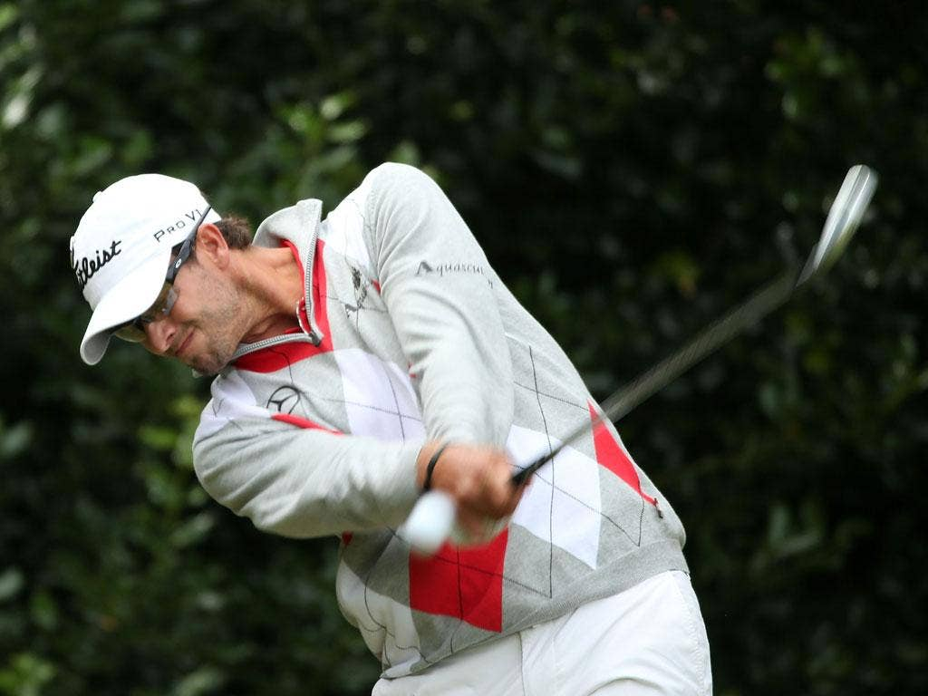 Adam Scott of Australia hits his tee shot on the first hole
