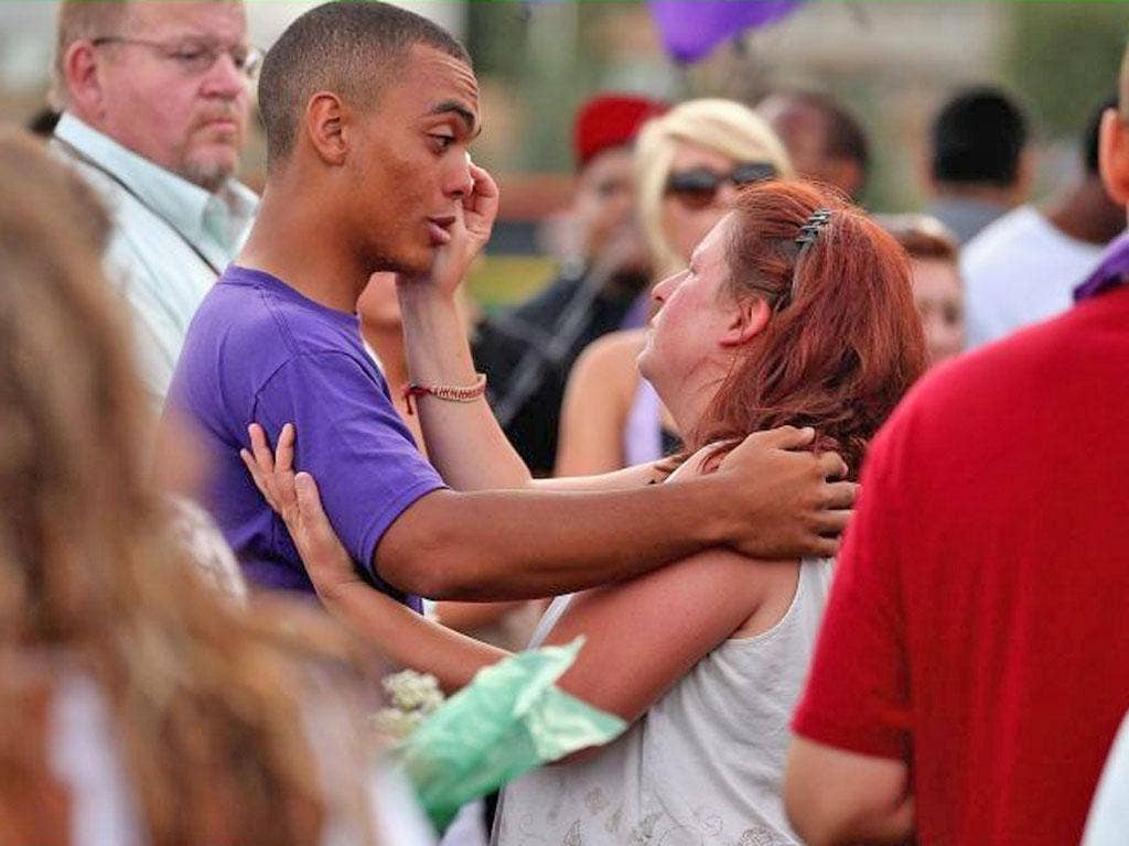 Shooting victim Alexander Boik's mother comforts one of her son's friends at a memorial service in Aurora, Colorado, on Saturday