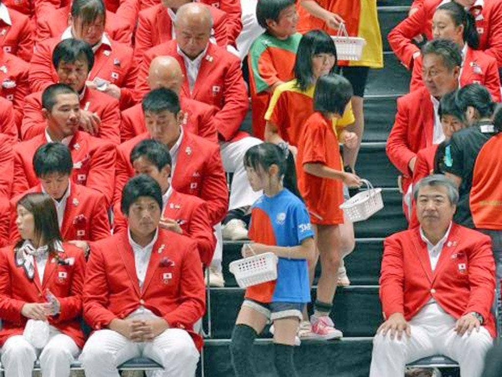 Children from the tsunami-hit regions hand out good-luck charms to Japan's Olympians at a ceremony in Tokyo