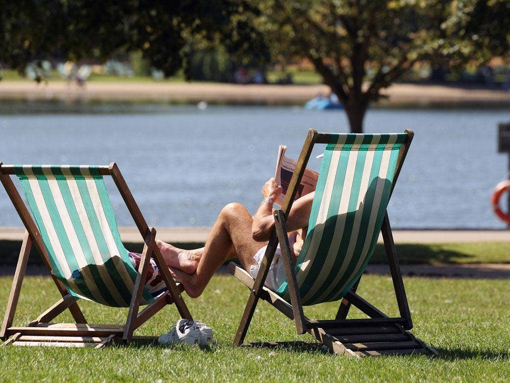 A man soaks up the sun in Hyde Park, London