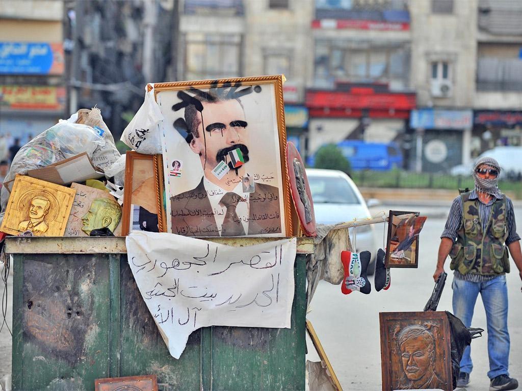 A Syrian rebel stands near a vandalized portrait of Syrian President Bashar al-Assad in the city center of Selehattin, near Aleppo,