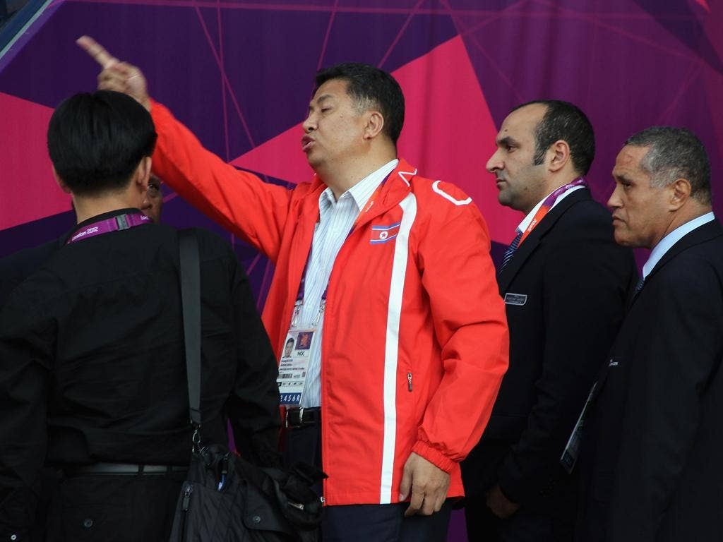 An official of DPR Korea gestures to the national flag as it is displayed wrongly